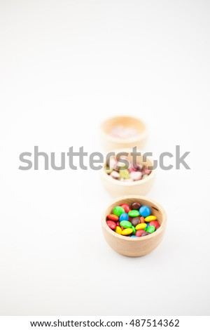 small colorful chocolate stones, chocolate drops in three wood cup on the white blackground