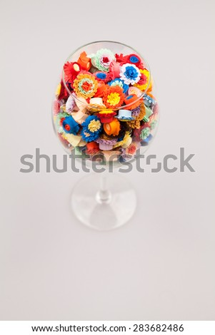 Small, colorful paper flowers made with quilling technique in a glass of wine