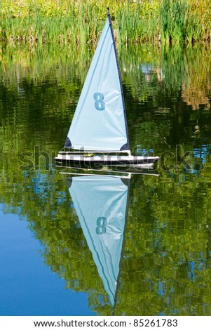 Small Competition Sailboat, with reflection on water.
