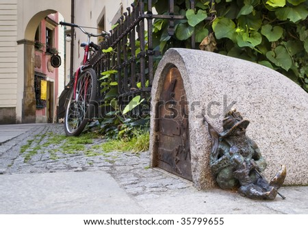 Small copper statue of a goblin, sitting on the floor of a street in Wroclaw, Poland - stock photo