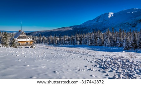Small cottage at the foot of the mountains in winter - stock photo