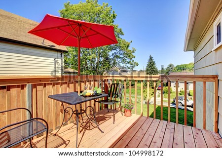 small cozy deck with red umbrella. - stock photo