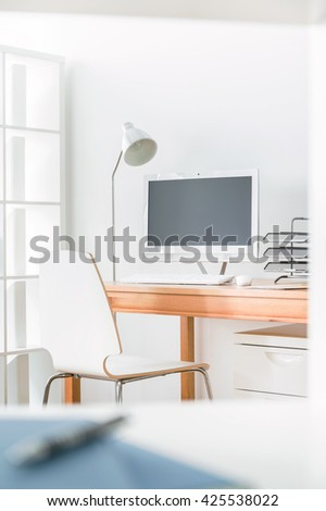 Small cozy work studio at home. In the corner of room wooden table with computer - stock photo