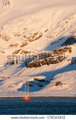 Small cruise ship at sunrise in Antarctica. - stock photo