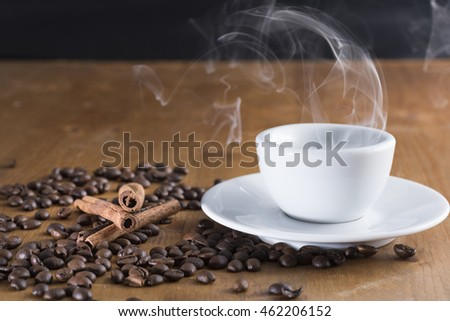 small cup reversed with coffee beans scattered on the wooden table