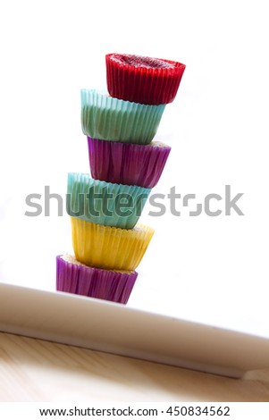 small cupcake in colorful cup place one on top of the other to create a column with a top cupcake - stock photo