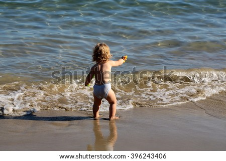 Small curious blonde child boy standing on sea coast beach with wavy water sunny twilight outdoor playing on natural background, horizontal picture - stock photo