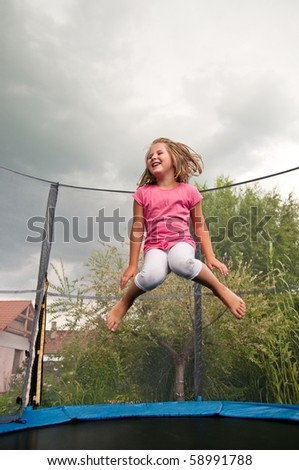Small cute child jumping on trampoline - garden and family house in background