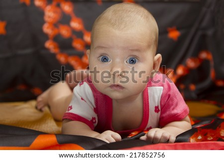 Small cute child surprised, raised his head and crawling on a dark bed - stock photo