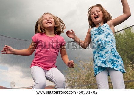 Small cute children jumping on trampoline - garden and family house in background
