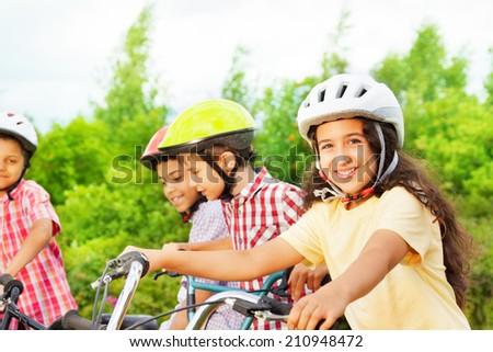 Small cute girl in helmet holds bike handle-bar - stock photo