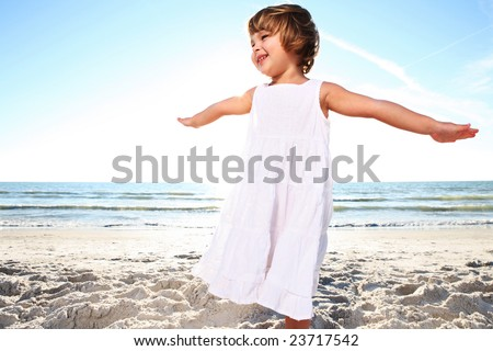 Small cute girl in white dress enjoying sunny day at the beach. Shoot against the sun. - stock photo
