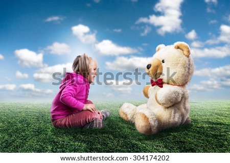 Small cute girl sits and looks at toy bear - stock photo