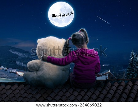 Small cute girl sitting on the roof with toy bear - stock photo