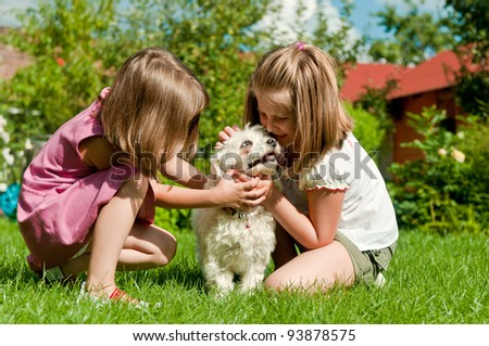 Small cute girls playing with her dog in garden behind family house - stock photo