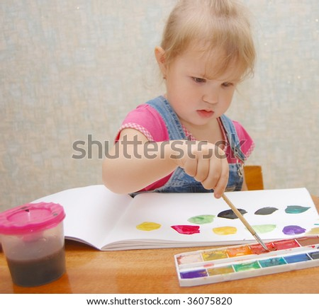 Small cute painting girl at home