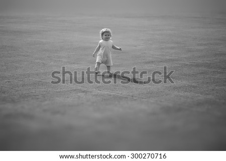 Small cute smiling baby boy with curly hair in light summer clothes maing step on field with fresh grass sunny day outdoor black and white copyspace, horizontal picture - stock photo