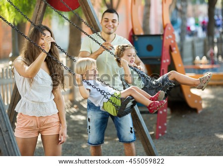 Small daughters on swings with young parents. Focus on woman - stock photo