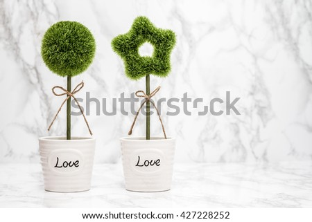 "Small decorative artificial green plants in white pots with ""Love"" text - stock photo"