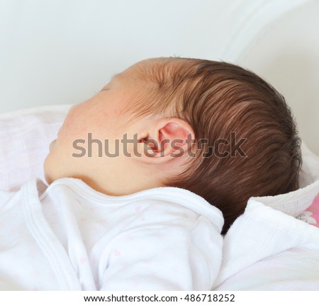 Small delicate little ear of newborn baby girl.