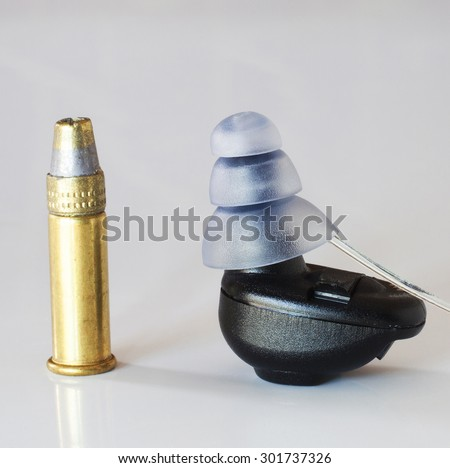 Small digital unit to protect your ears next to a .22 cartridge for scale - stock photo