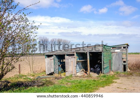 Small dilapidated wooden barn in the Netherlands on a sunny day in the spring season. - stock photo