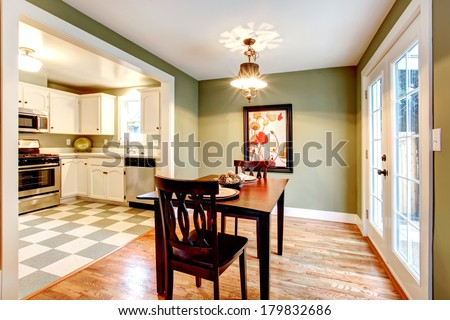 Small dining room with a hardwood floor and olive walls. Furnished with a black dining table set. View of the kitchen.