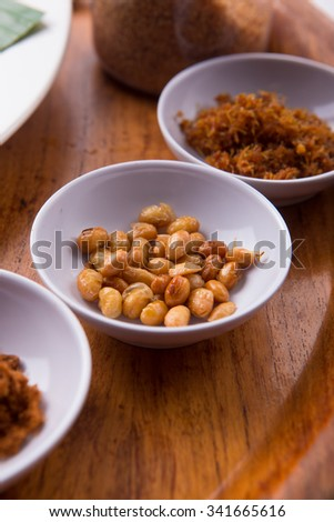 Small dishes: beef floss, fried soy beans, sweet and savory tempeh, traditional foods from indonesia and malaysia - stock photo