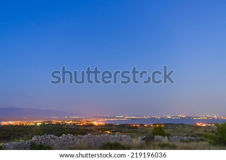 Small distant town by the night at Adriatic sea.  - stock photo