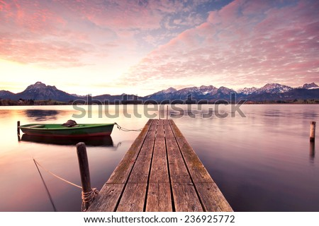 Small Dock and Boat at the lake, sunrise in autumn - stock photo