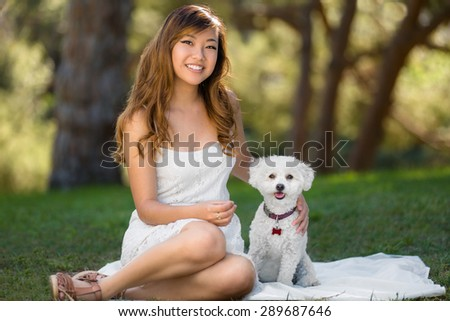 Small dog sitting next to beautiful owner outdoors at the park on a perfect day - stock photo