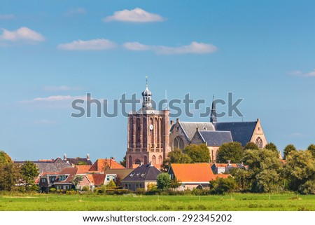 Small Dutch village with an old large church in the province of Friesland - stock photo