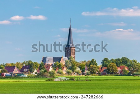Small Dutch village with church in the province of Friesland - stock photo