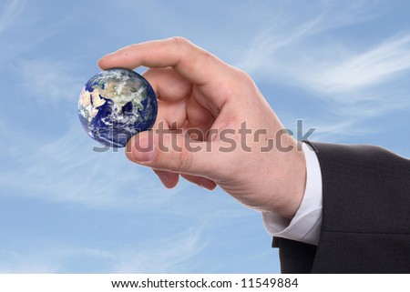 small earth in a hand on background blue sky - stock photo