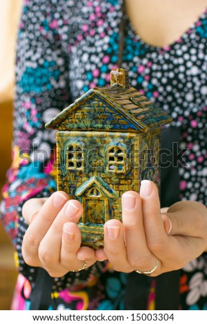 Small earthenware house in woman hands isolated on white background