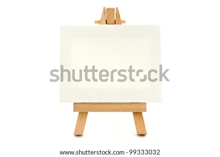 Small easel with a blank canvas over white - stock photo