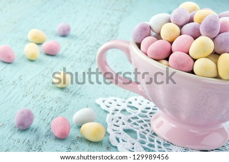 Small easter eggs in a pink cup on light blue wooden table - stock photo