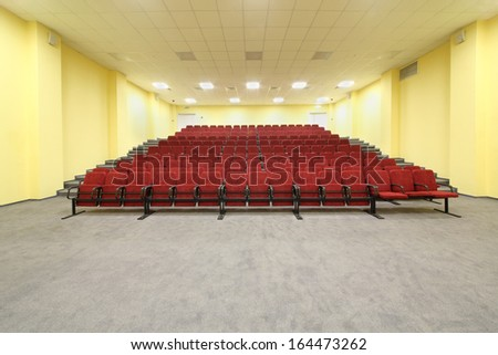 Small empty concert hall with red armchairs and yellow walls. - stock photo