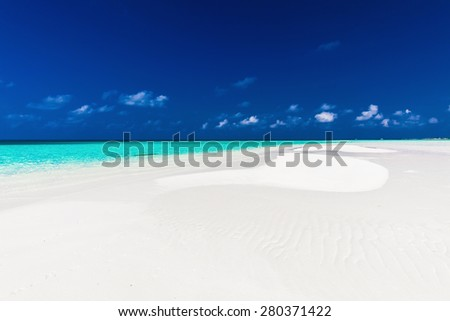 Small empty sandbar in the middle of tropical lagoon in atoll of Maldives - stock photo