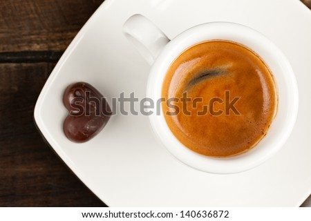Small espresso cup and chocolate heart, against polished table top - stock photo