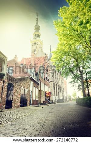 Small European town street with cobblestone pavement  - stock photo