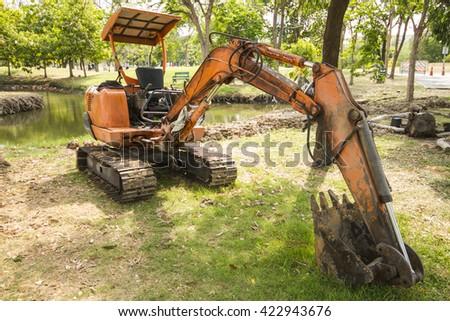 small excavator in green garden. - stock photo