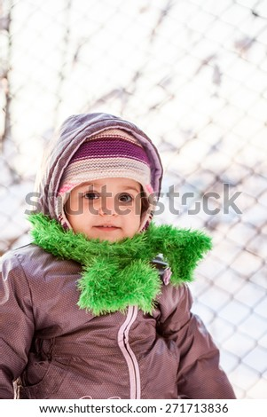 Small, expressive baby girl dressed for winter, with winter background - stock photo