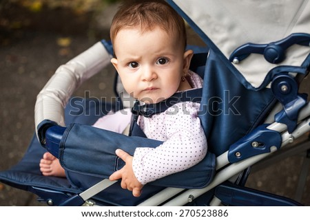 Small, expressive baby girl in a baby carriage with natural light in the park - stock photo