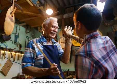 Small family business and traditions: old grandpa with grandson in lute maker shop. The senior artisan gives five to the boy, who helps him to make a handmade music instrument - stock photo