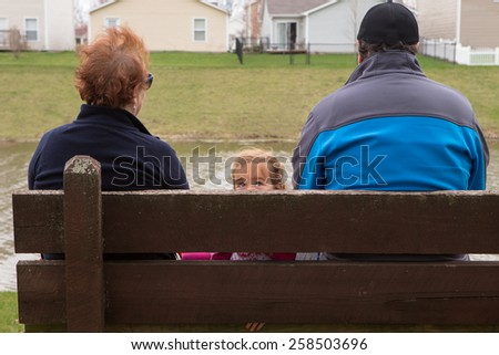 Small Family Sitting on a Wooden Bench at the Park Looking Different Directions. - stock photo