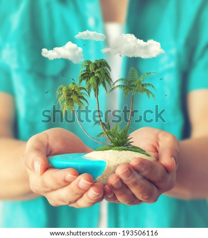 Small fantastic island with tropical palms in men's hands.