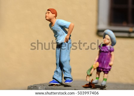 Small figurine two children play in garden.