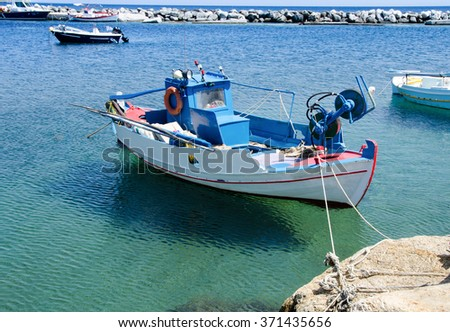 Small fishing boat floating in clear waters - stock photo