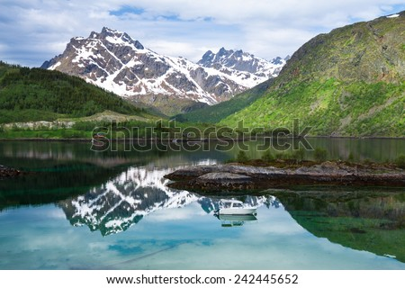 Small fishing boat in scenic fjord on Lofoten islands, Norway - stock photo
